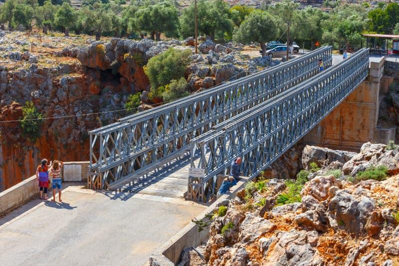 De niet geïdentificeerde mensen bezoeken beroemde bundelbrug over Aradena-Kloof op het Eiland van Kreta, Griekenland stock fotografie