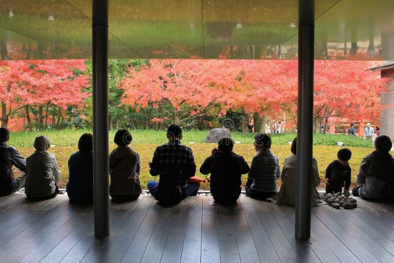 De niet geïdentificeerde mensen rusten bij een Zen-tuinbinnenkant byodo-in Tempel stock foto