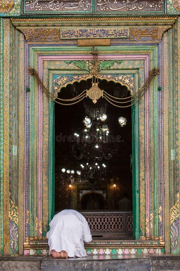 De niet geïdentificeerde moslimmens bidt bij de ingang aan de oude moskee khanqah-e-Moula in oude stad van Srinagar, Jammu en Kas stock afbeelding