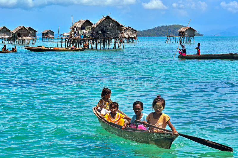 De niet geïdentificeerde overzeese zigeunersjonge geitjes paddelen een boot in Semporna, Sabah, Maleisië stock foto's