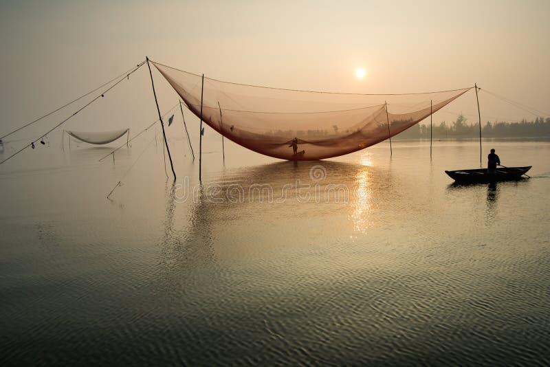 De niet geïdentificeerde visser controleert zijn netten in vroege ochtend op rivier in Hoian, Vietnam stock foto