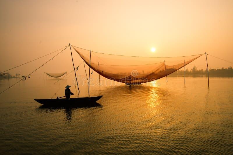 De niet geïdentificeerde visser controleert zijn netten in vroege ochtend op rivier in Hoian, Vietnam royalty-vrije stock foto