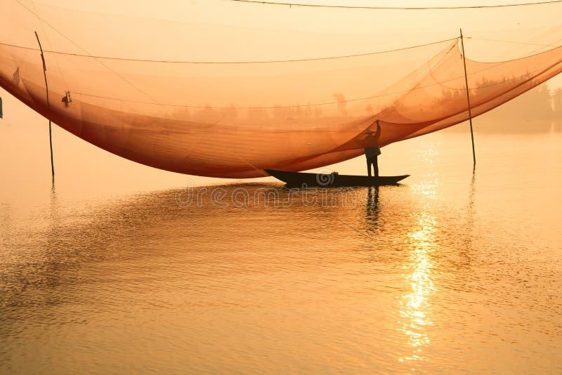 De niet geïdentificeerde visser controleert zijn netten in vroege ochtend op rivier in Hoian, Vietnam royalty-vrije stock foto's