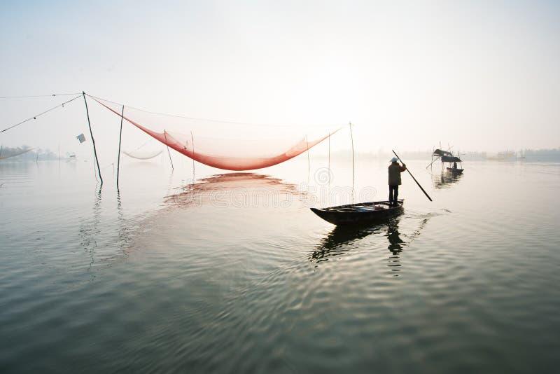 De niet geïdentificeerde visser controleert zijn netten in vroege ochtend op rivier in Hoian, Vietnam stock foto's