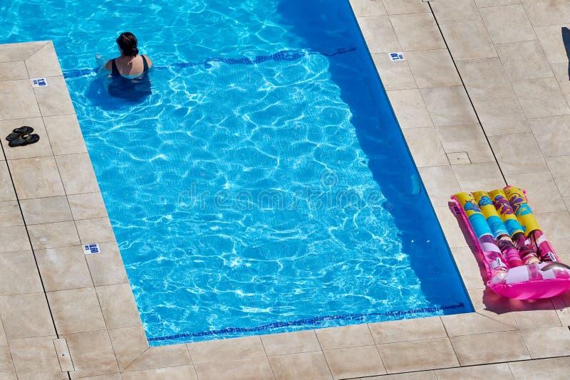De niet geïdentificeerde vrouw calmt zich in een zwembad op een het schroeien hete dag royalty-vrije stock afbeeldingen