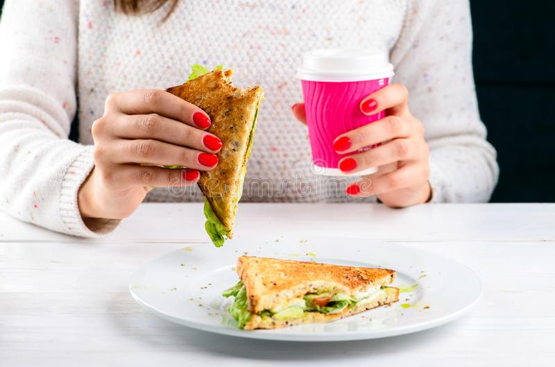 De Niet geïdentificeerde vrouw die van de lunchtijd BLT-sandwich eten stock afbeelding