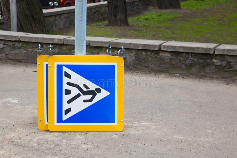 De nieuwe geel-blauwe verkeersteken ` voetgangersoversteekplaats ` ligt op de grond tegen de achtergrond van de weg Klaar voor ge royalty-vrije stock fotografie