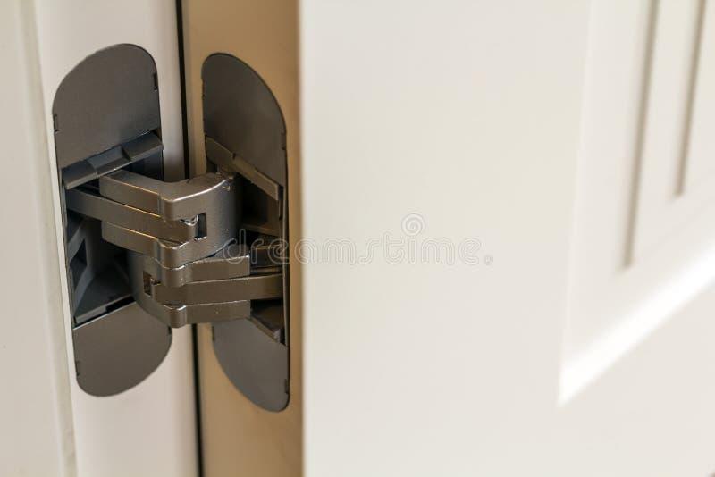De nieuwe moderne scharnieren van de metaaldeur op witte houten deuren stock afbeeldingen
