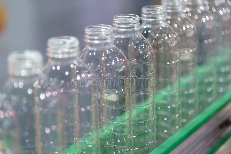 De nieuwe plastic flessen op de transportband royalty-vrije stock afbeelding