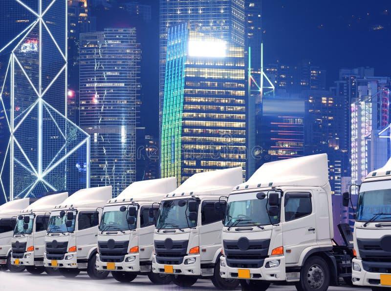 De nieuwe vrachtwagenvloot parkeert voor de Grote stad in bedrijfsdistrict zoals voor vervoer royalty-vrije stock afbeeldingen