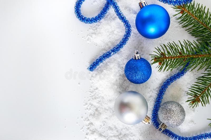 De nieuwjaarbanner met blauwe en zilveren Kerstmisballen in sneeuw, dirkt groene takken op witte achtergrond op De decoratie van  royalty-vrije stock afbeelding