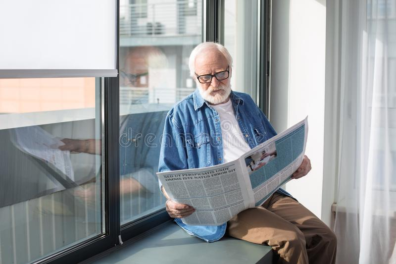 De nieuwsgierige gebaarde krant van de gepensioneerdelezing op vensterbank stock foto