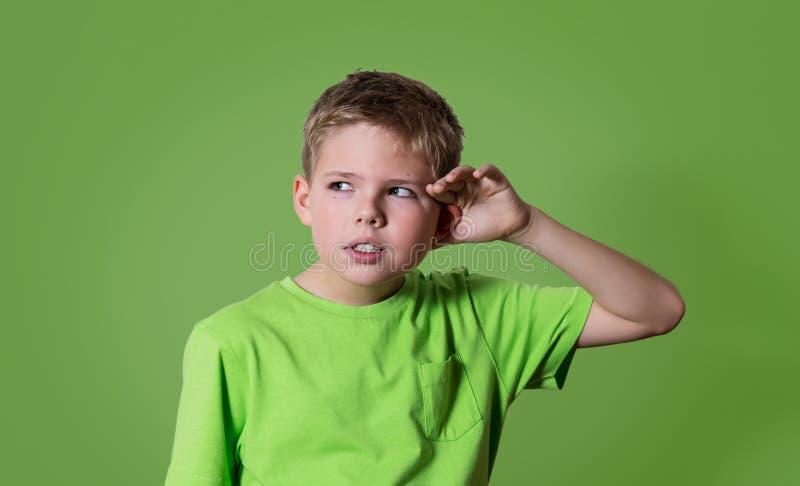 De nieuwsgierige jongen luistert De het kindhoorzitting van het close-upportret iets, ouders spreekt, roddels, hand aan oorgebaar stock foto