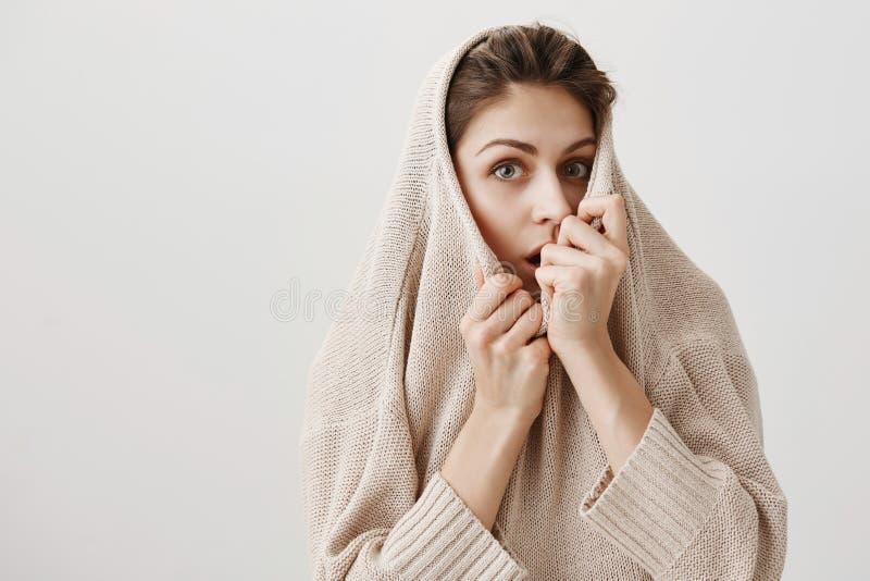 De nieuwsgierige vrouw wil rest van eng verhaal horen Charmante volwassen Kaukasische vrouwelijke trekkende sweater op gezicht en stock foto