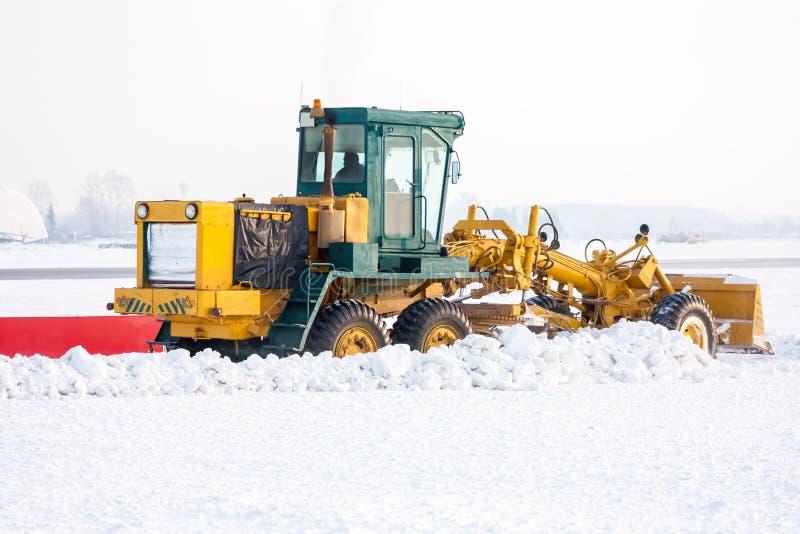 De nivelleermachine ontruimt sneeuw op de taxibaan bij de luchthaven royalty-vrije stock foto