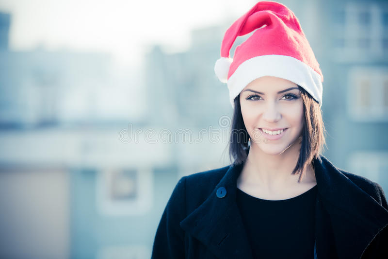 De Noël de Santa de chapeau portrait de sourire de femme dehors Fille heureuse de sourire utilisant son chapeau de Santa avec le  photographie stock libre de droits