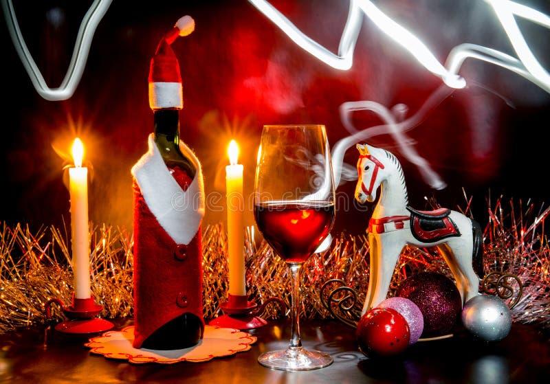 De Noël toujours la vie avec une bouteille de vin, des bougies et des glas d'un vin photographie stock