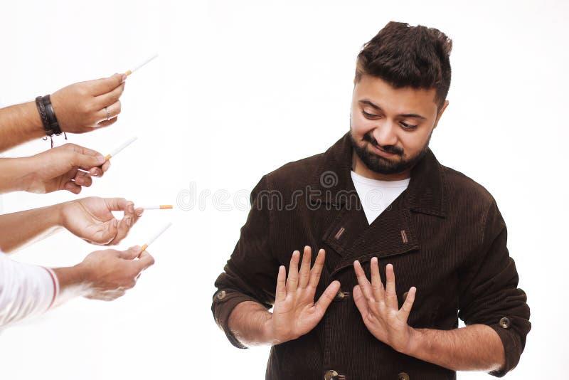 De no fumadores Hombre joven que rechaza el cigarrillo aislado en blanco imagen de archivo libre de regalías
