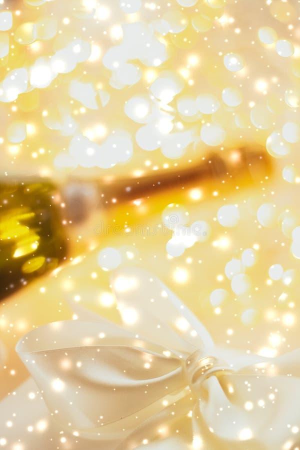 De Noche Vieja del día de fiesta la botella del champán y una nieve del caja de regalo y brillante en el fondo de mármol foto de archivo libre de regalías