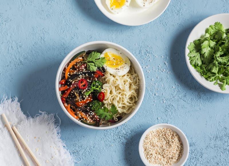 De noedels met groente bewegen gebraden gerecht en gekookt ei Vegetarisch voedsel in Aziatische stijl Op een blauwe achtergrond stock fotografie