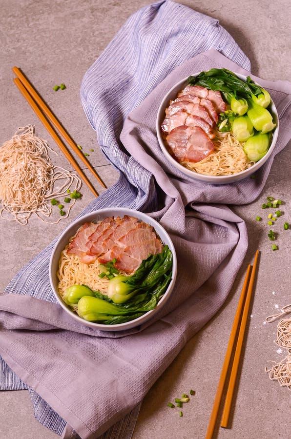 De noedels van het plakvarkensvlees met groenten op servetten stock afbeeldingen