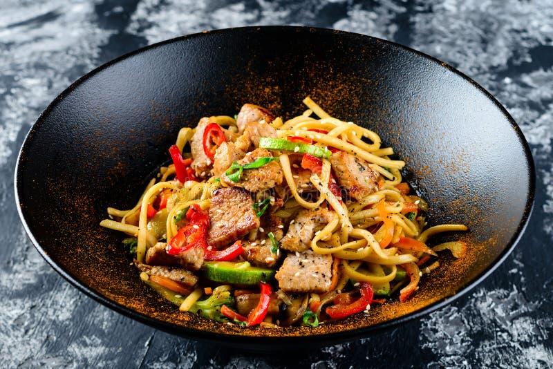 De noedels van het Udon be*wegen-gebraden gerecht met kippenvlees en sesam in kom stock afbeeldingen