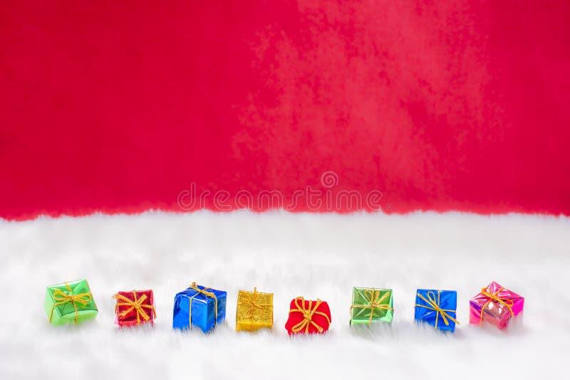 De nombreux cadeaux de Noël colorés dans la neige photos stock