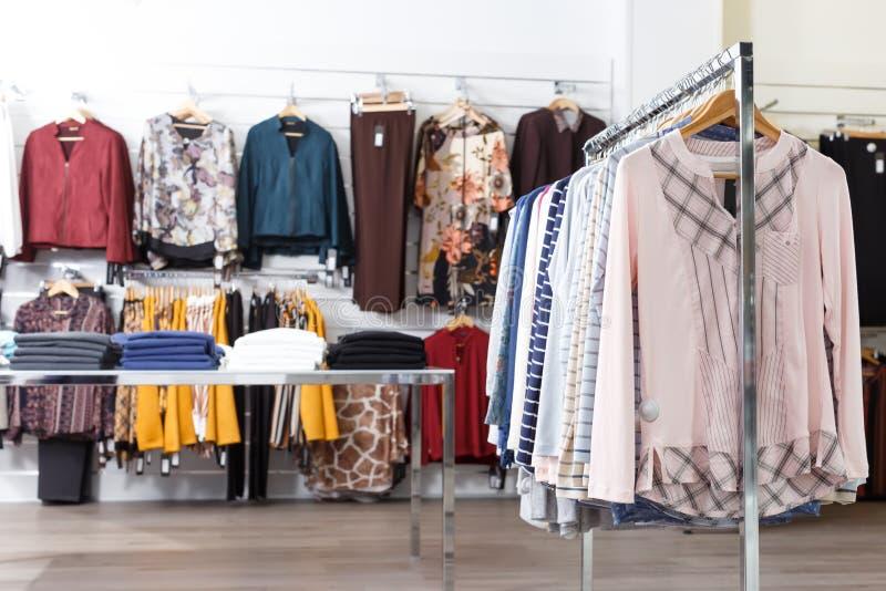 De nombreux vêtements élégants sur les cintres et les étagères photos libres de droits