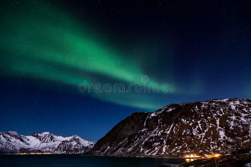 De noordelijke lichten over de bergen en de oceaan royalty-vrije stock foto