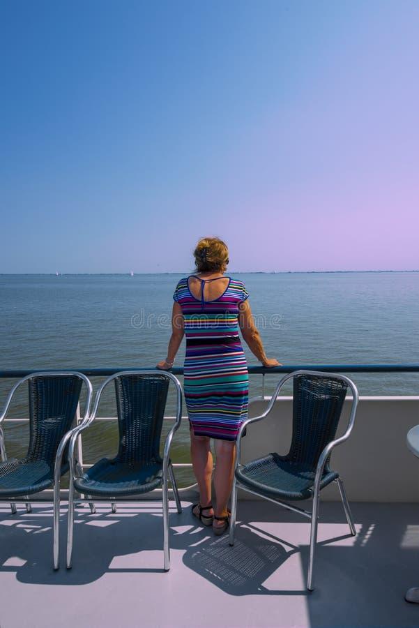 De Noordzee zich Nederland 26 Vrouw juli-2018 bevindt bij het traliewerk van een schip dat zeilen op een kalme oceaan in de zomer royalty-vrije stock foto's