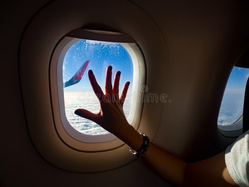 De nostalgische hand van de vrouwenpassagier wat betreft vliegtuigvenster met mening van vleugel royalty-vrije stock foto