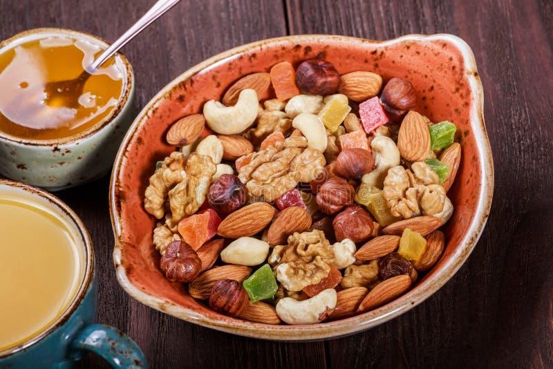 De noten mengen zich in een kom, een kop thee en een honing op donkere houten dichte omhooggaand als achtergrond Okkernoten, pist royalty-vrije stock afbeelding