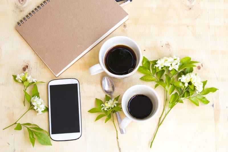 De notitieboekjeontwerper, de mobiele telefoon voor het bedrijfswerk en de hete koffieespresso brengen kop samen stock afbeelding