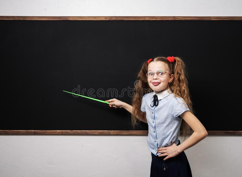 De nouveau à l'école : Écolière de fille dans l'uniforme scolaire se tenant au tableau noir avec un indicateur et des expositions images stock