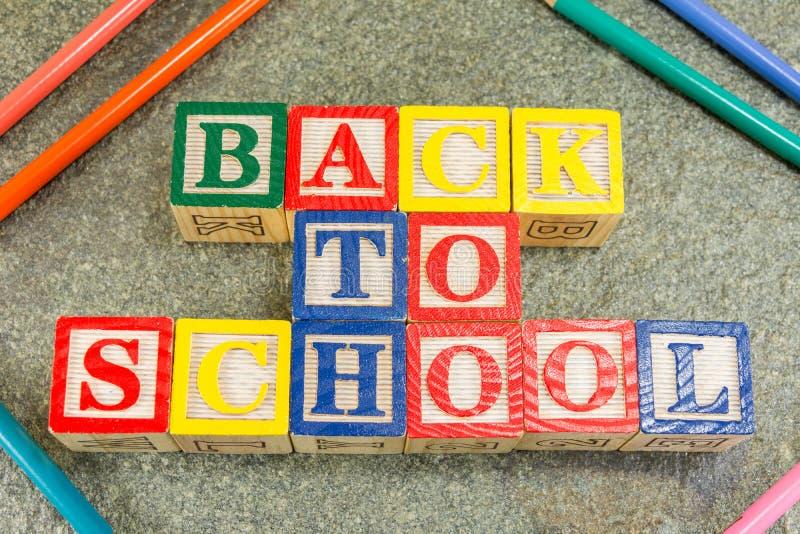 De nouveau à l'école écrite avec les lettres cubiques en bois images stock