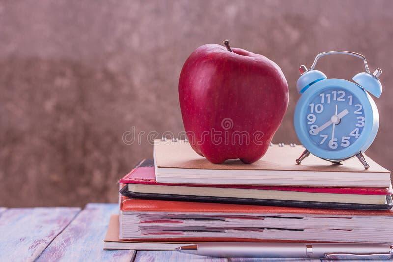 De nouveau à l'école, carnet, réveil, pomme rouge, fleur sur en bois image libre de droits