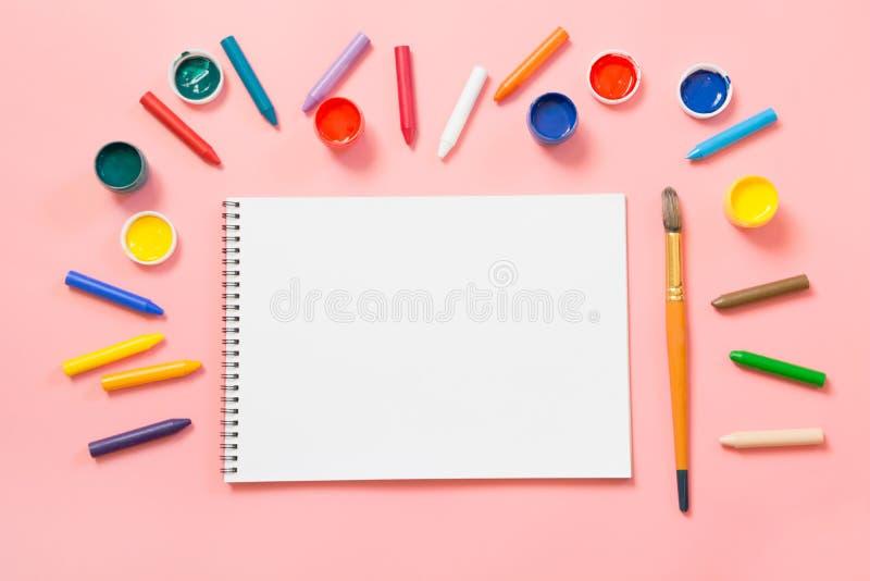 De nouveau à l'école Crayons, album et brosse colorés de cire sur le rose ivre Copiez l'espace Vue supérieure photo libre de droits
