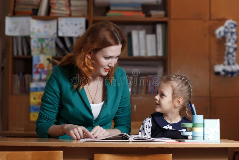 De nouveau à l'école L'enfant apprend à écrire La femme adulte enseigne à enfant l'alphabet image stock