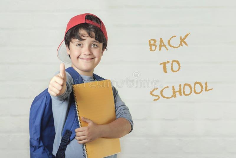 De nouveau à l'école, à l'enfant heureux avec le sac à dos et avec le carnet photo libre de droits
