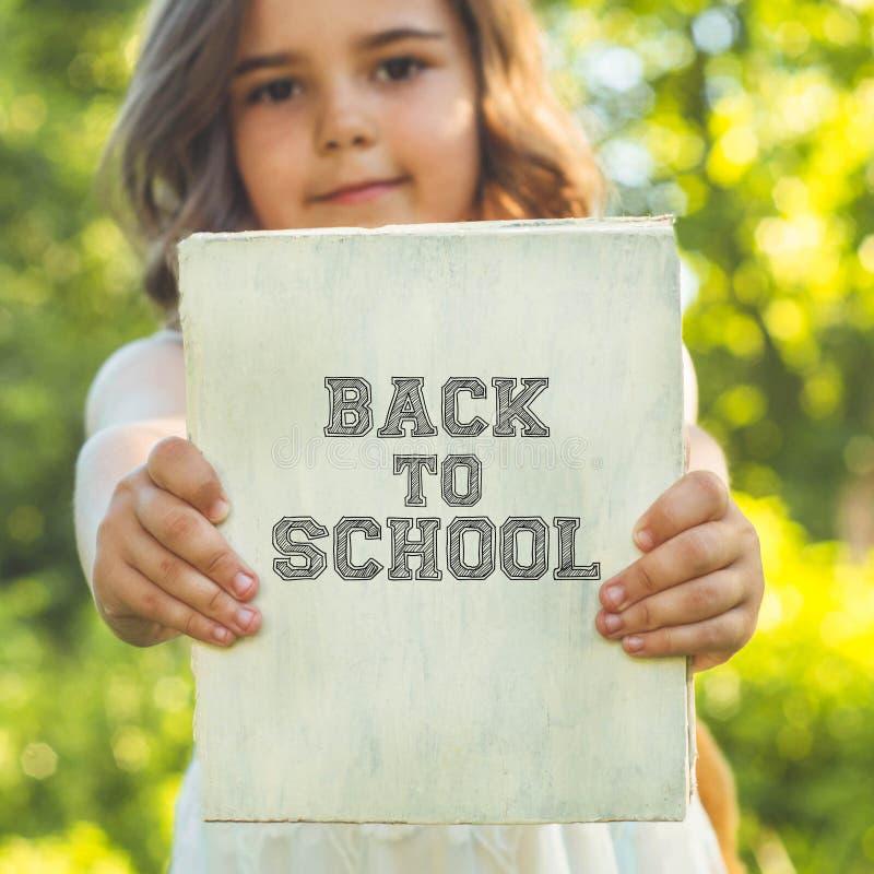 De nouveau à l'école et au temps heureux ! L'enfant travailleur mignon se tient avec un livre et une serviette photographie stock