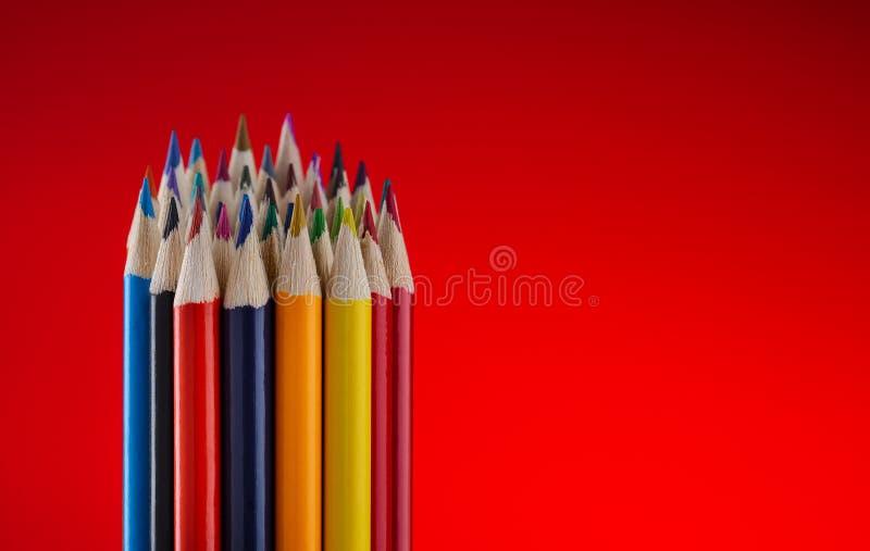 Crayons de couleur sur le fond rouge photo stock