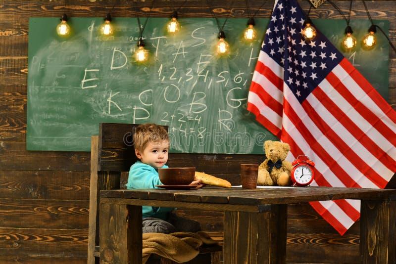 De nouveau à l'école ou à l'enseignement à domicile Instruisez l'enfant à la leçon dans le 4ème juillet Le petit garçon mangent d photos stock