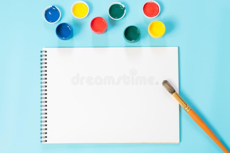 De nouveau à l'école Peintures, album et brosse colorés sur le bleu ivre Copiez l'espace Vue supérieure photographie stock