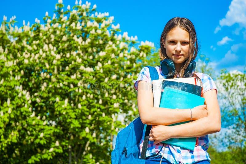 De nouveau à la fille d'adolescent d'étudiant d'école jugeant des livres et des carnets utilisant le sac à dos Extérieur en parc photographie stock libre de droits