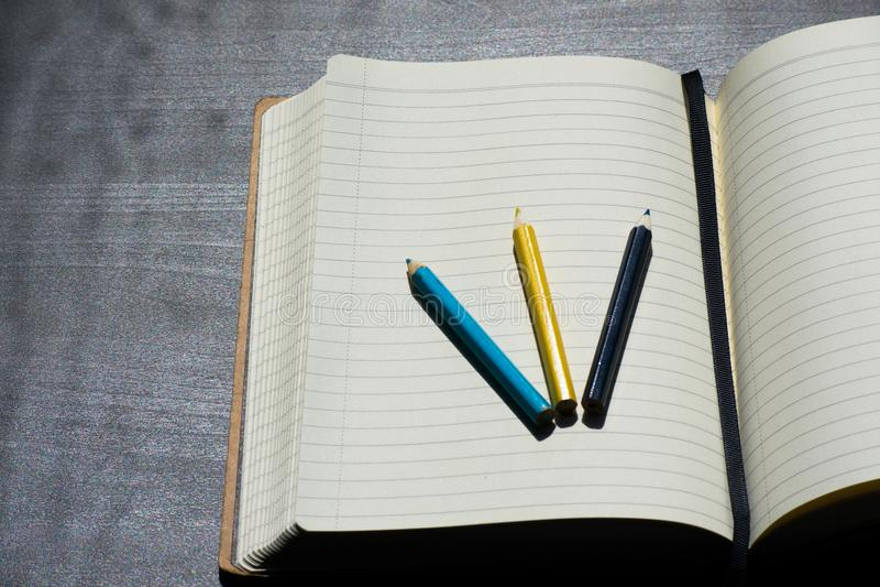 De nouveau au carnet jaune bleu de couleur de crayon de crayon de Noteblock d'école image stock