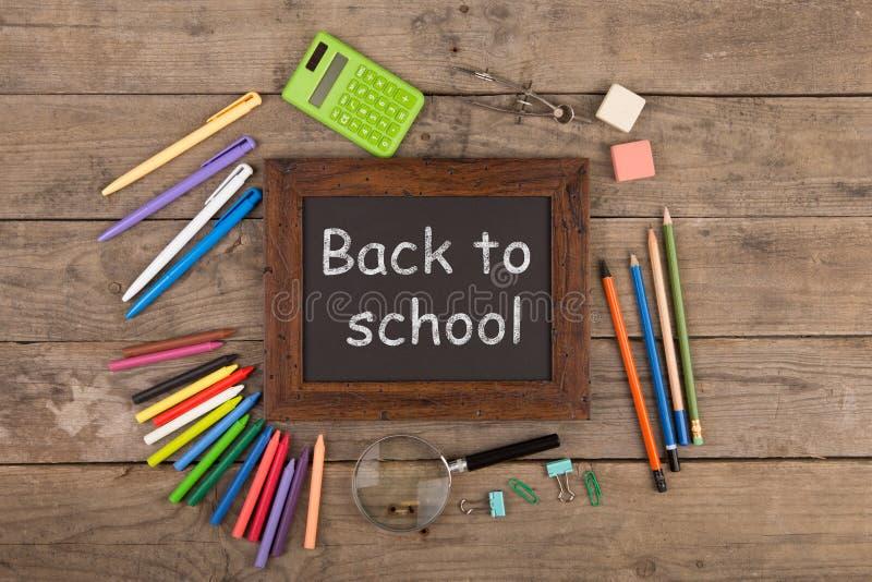 De nouveau au concept d'école - fournitures scolaires sur le bureau en bois image stock
