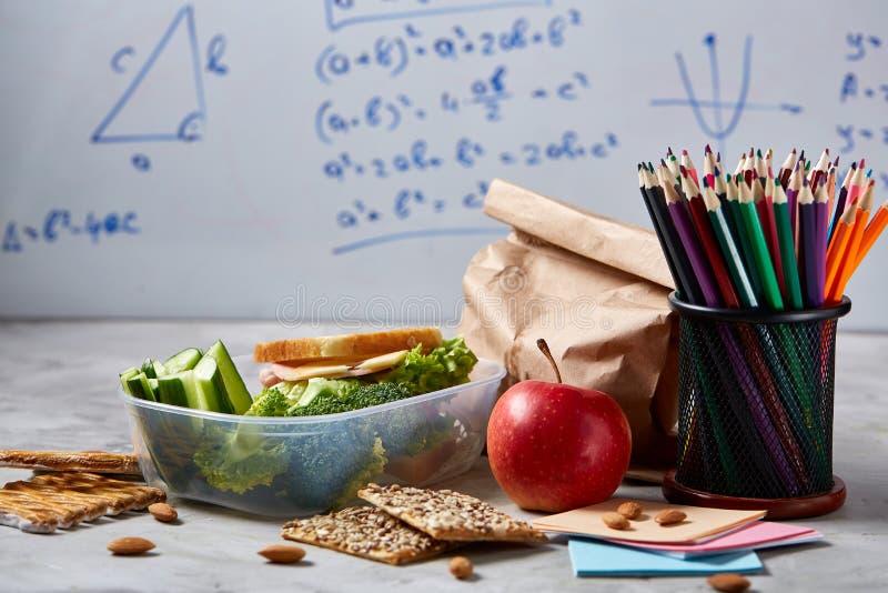 De nouveau au concept d'école, les fournitures scolaires, biscuits, ont emballé le déjeuner et le panier-repas au-dessus du table images stock