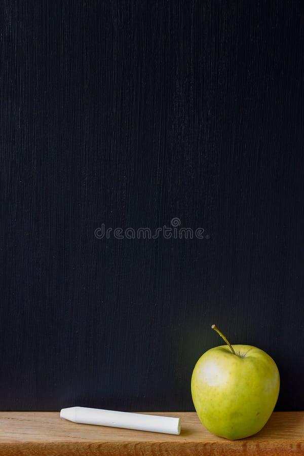 De nouveau au concept d'école, au plan rapproché d'un panneau de craie noir propre, à la craie blanche et à une pomme verte, foye photographie stock
