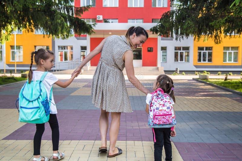 De nouveau au concept d'éducation d'école avec des enfants de fille, étudiants élémentaires, sacs à dos de transport allant class photo libre de droits