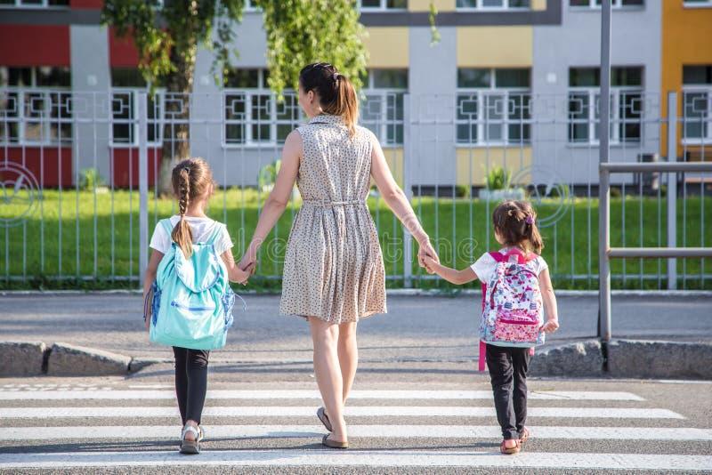 De nouveau au concept d'éducation d'école avec des enfants de fille, étudiants élémentaires, sacs à dos de transport allant class image stock